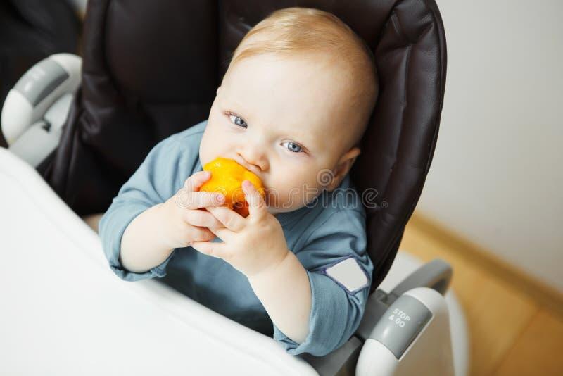 Le bébé s'assied dans le highchair et mange la pêche photos libres de droits