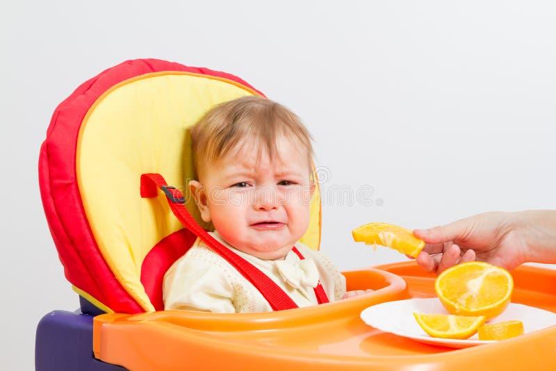Le bébé s'assied dans le highchair avec l'orange images stock