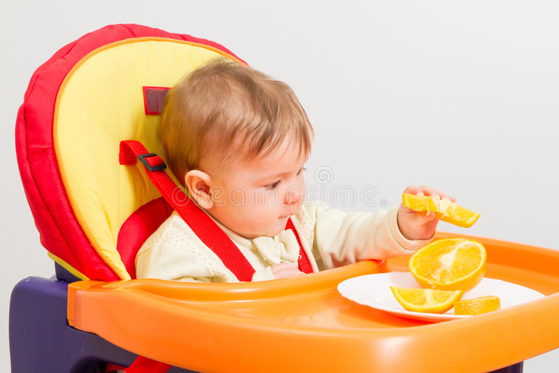 Le bébé s'assied dans le highchair avec l'orange photographie stock