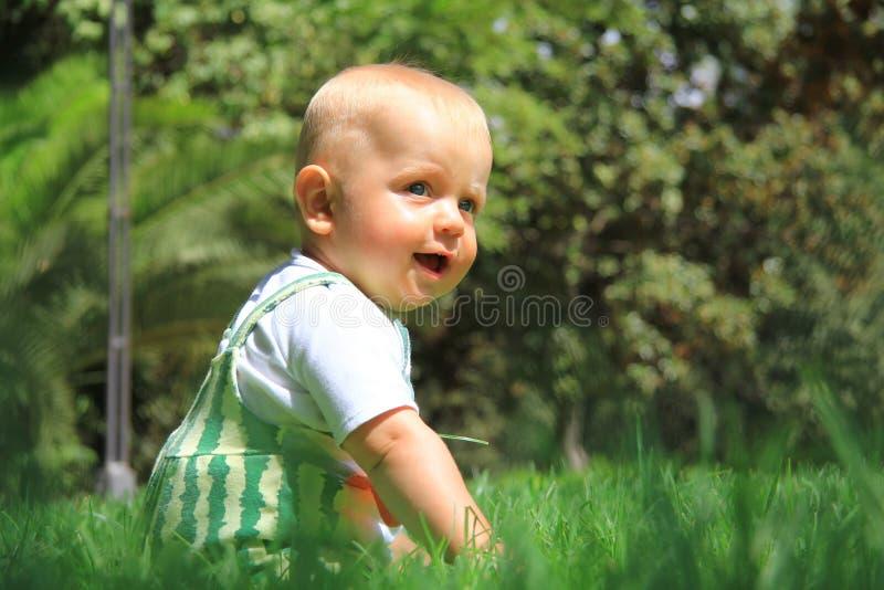 Le bébé s'assied sur une herbe images libres de droits