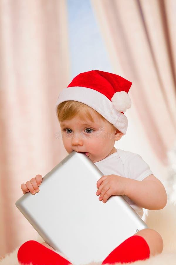 Le bébé Santa tient un comprimé photo libre de droits
