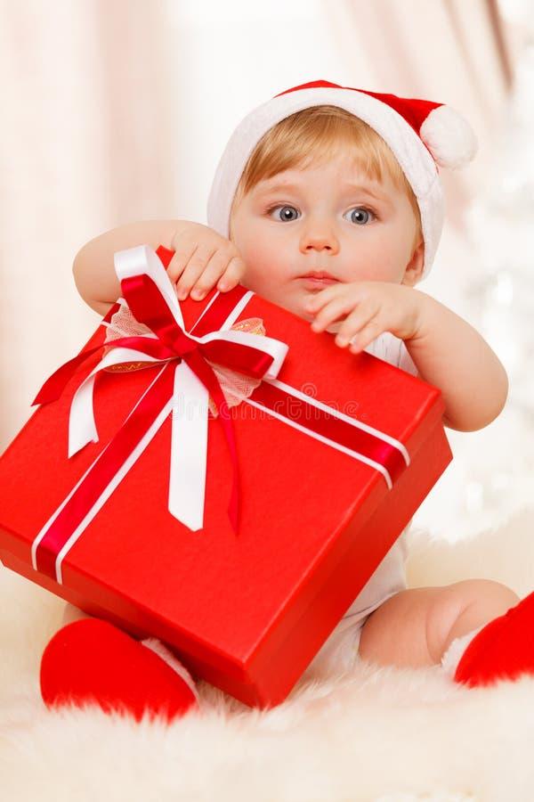 Le bébé Santa tient un grand boîte-cadeau rouge images libres de droits