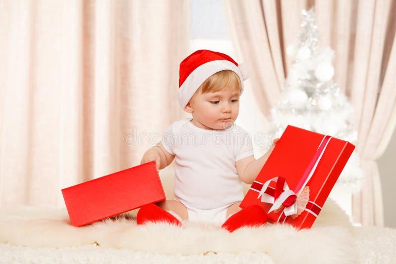 Le bébé Santa tient un grand boîte-cadeau rouge photo libre de droits