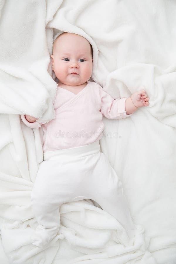 Le bébé se trouve sur la couverture blanche images libres de droits