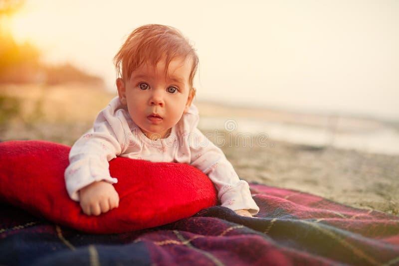 Le bébé se trouve sur le plaid et a lu l'oreiller en parc image stock