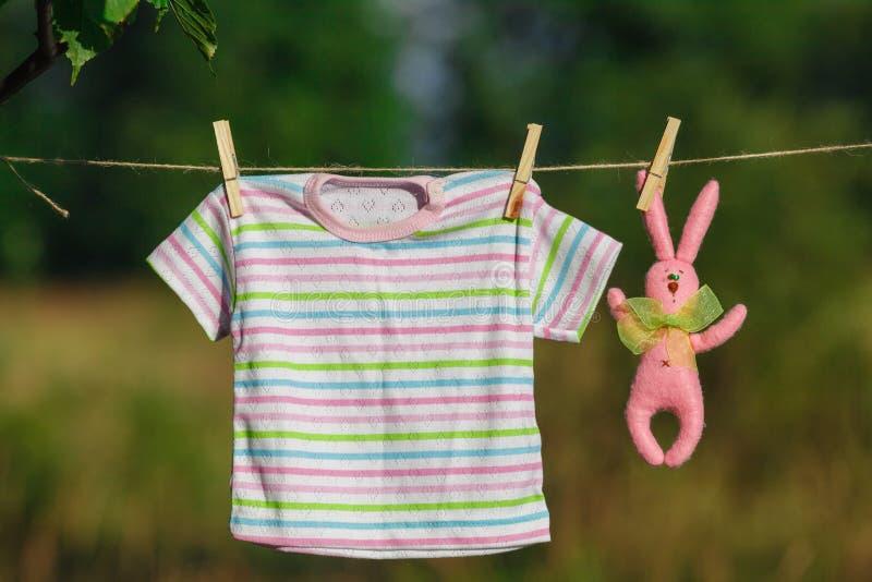 Le bébé vêtx accrocher et sécher du jardin image stock