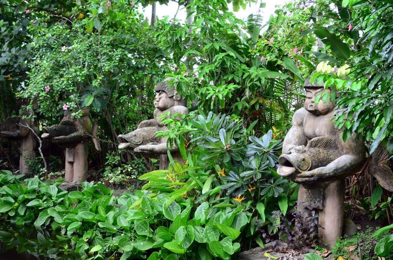 Le béton énorme a découpé la statue de l'homme d'habitant des îles du Pacifique tenant des poissons dans la jungle image stock