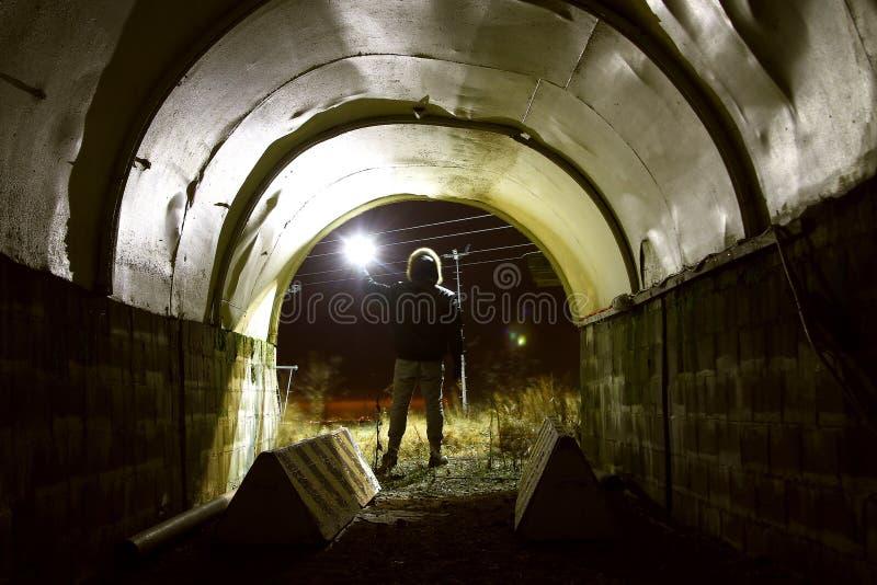 Le bêcheur avec la lanterne dans le tunnel sombre a allumé - Diggery dans une salle industrielle abandonnée images libres de droits
