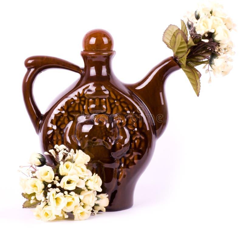 Le bac d'argile avec des fleurs a isolé image stock
