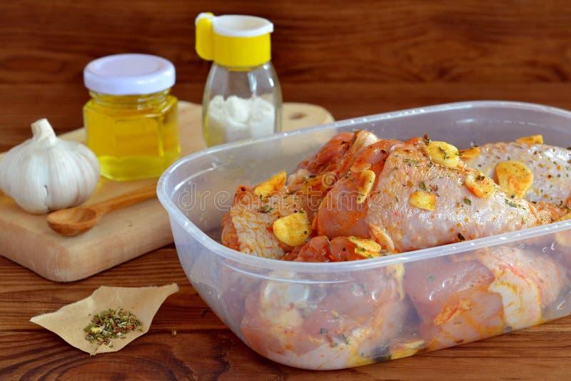 Le bacchette di pollo crude con le spezie, l'olio d'oliva, l'aglio, sale hanno preparato per friggere Ingredienti per la cottura  immagine stock libera da diritti