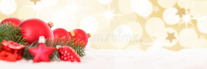 Le bagattelle dorate rosse della decorazione delle palle di Natale stars la neve dell'insegna fotografie stock libere da diritti