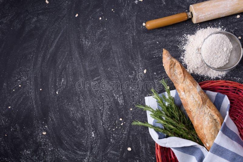 Le baguette francesi con i rosmarini avvolti in un asciugamano in canestro rosso e l'intero grano flour, matterello su fondo rust fotografie stock