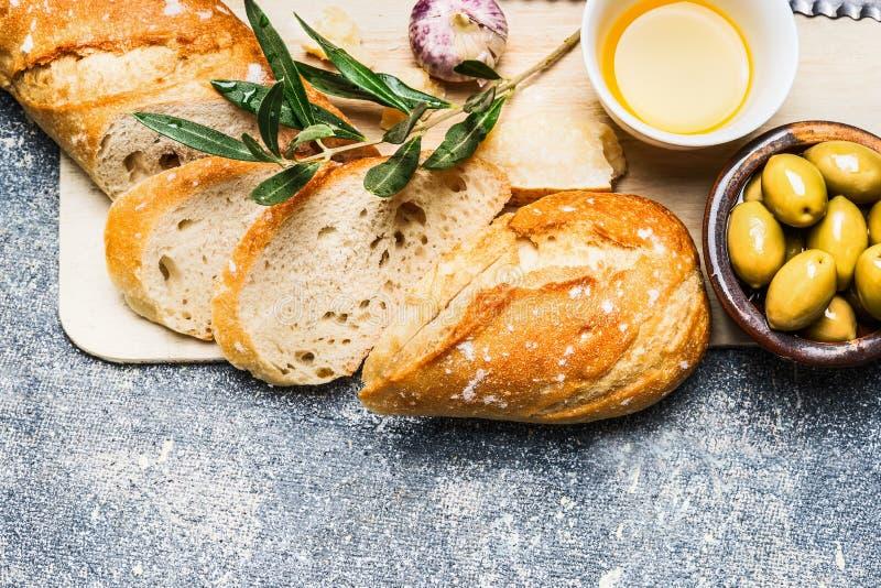Le baguette hanno tagliato nelle fette sul tagliere, sulle olive, sull'aglio e sul formaggio di legno su fondo rustico immagine stock libera da diritti