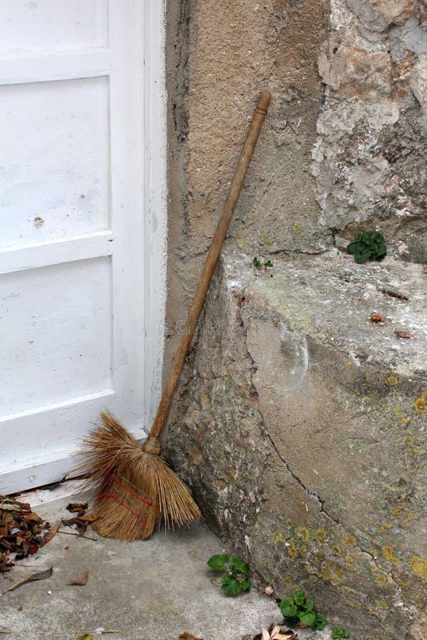 Le balai fortement utilisé de maison est parti dans l'arrière-cour après utilisation penchée sur le mur en pierre délabré criqué  image libre de droits