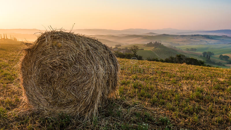 Le balle di fieno su un'estate sistema all'alba in Toscana fotografia stock