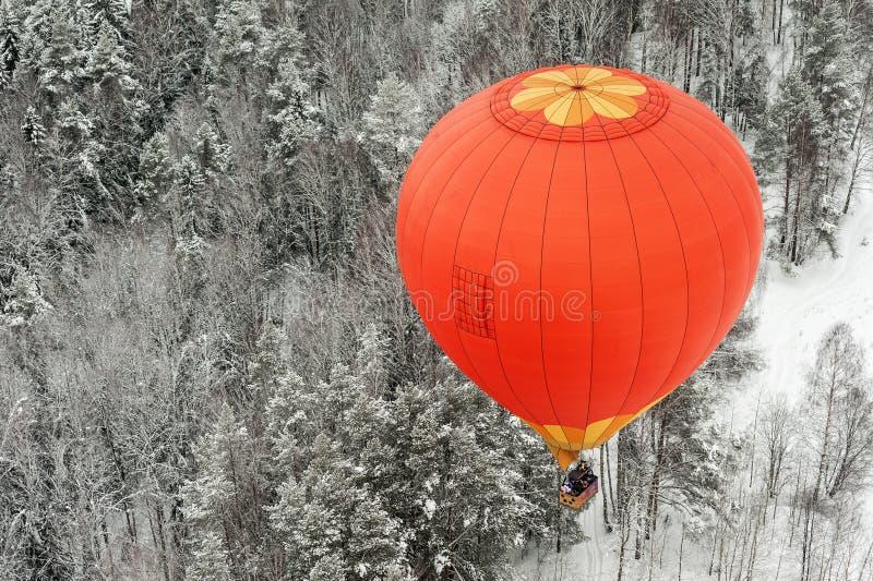 Le ballon à air chaud vole au-dessus d'une forêt d'hiver photos libres de droits