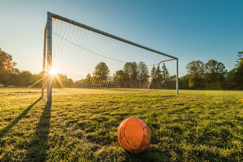 Le ballon de football vibrant a centré devant le but du football au sunr images stock