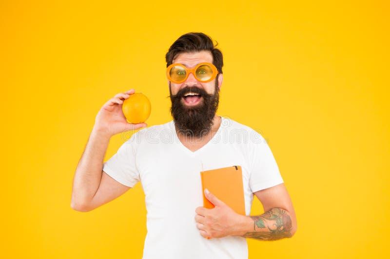 Le ballot est le nouveau se refroidissent Homme barbu de ballot Livre de participation de ballot d'étude et fruit orange sur le f photos stock