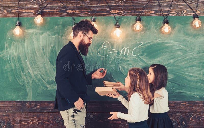 Le bambine ascoltano l'uomo barbuto al consiglio scolastico L'insegnante scrive con gesso sulla lavagna L'istitutore insegna ai b fotografia stock