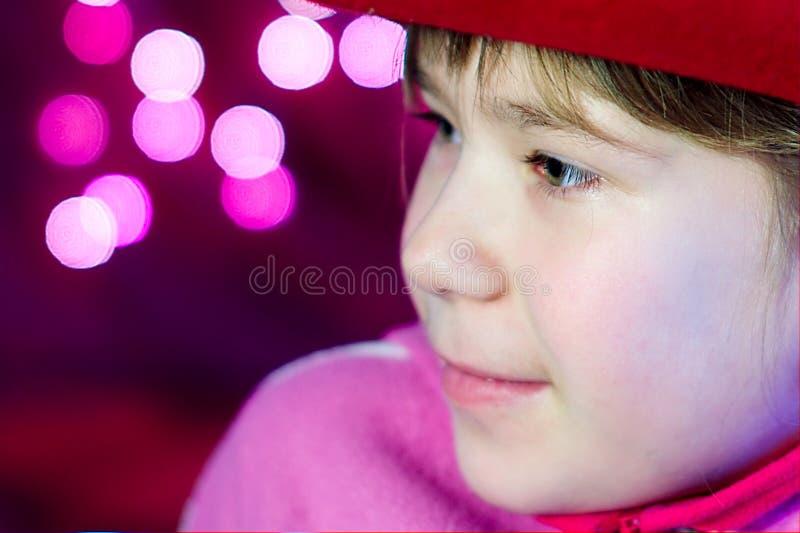 Le bambine osservano con gli indicatori luminosi di natale immagini stock