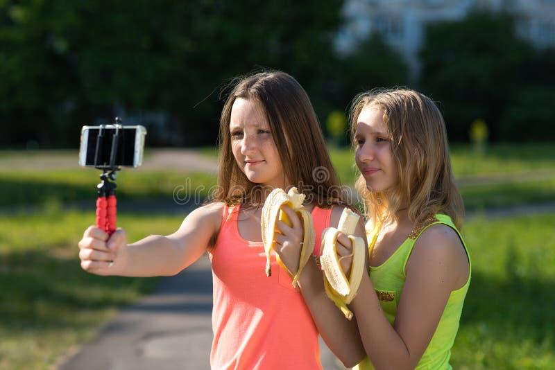 Le bambine sono adolescenti Estate in natura Tiene le banane in sue mani e le mangia Tiene uno smartphone sulla a fotografia stock libera da diritti