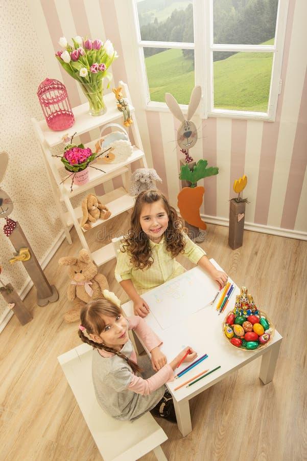 Le bambine sono fatte di Pasqua - dipingono, essi assorbono la stanza fotografia stock libera da diritti