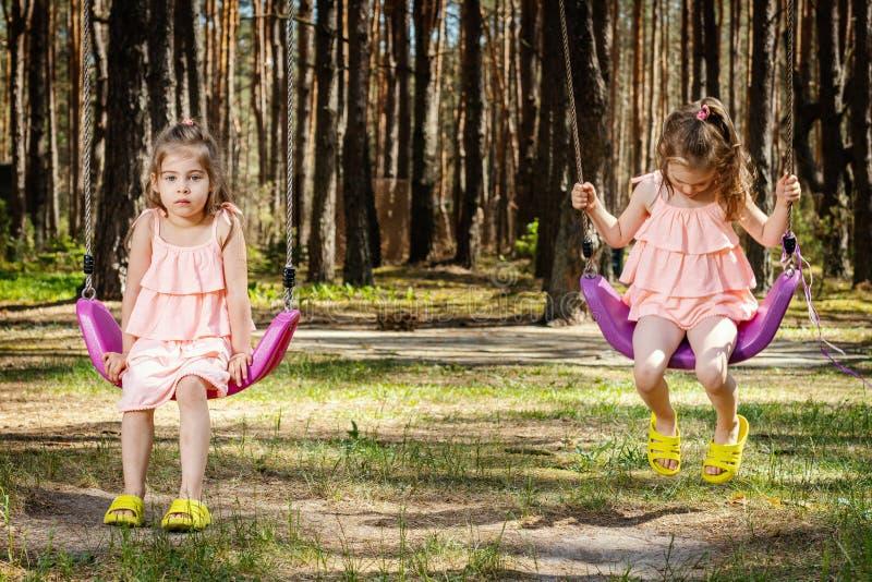Le bambine stanno oscillando sulle oscillazioni immagine stock