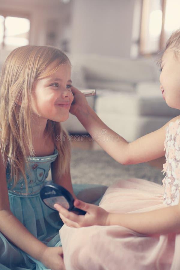 Le bambine sveglie che giocano con compongono nella stanza fotografia stock