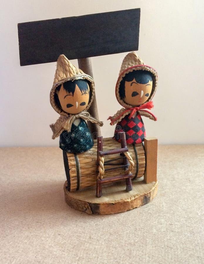 Le bambole giapponesi del ragazzo e della ragazza del primo piano sono fatte da legno si siedono sul barilotto di legno fotografia stock