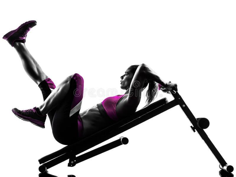 Le banc à presse de forme physique de femme craque des exercices image libre de droits