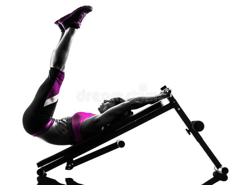 Le banc à presse de forme physique de femme craque la silhouette d'exercices photos stock