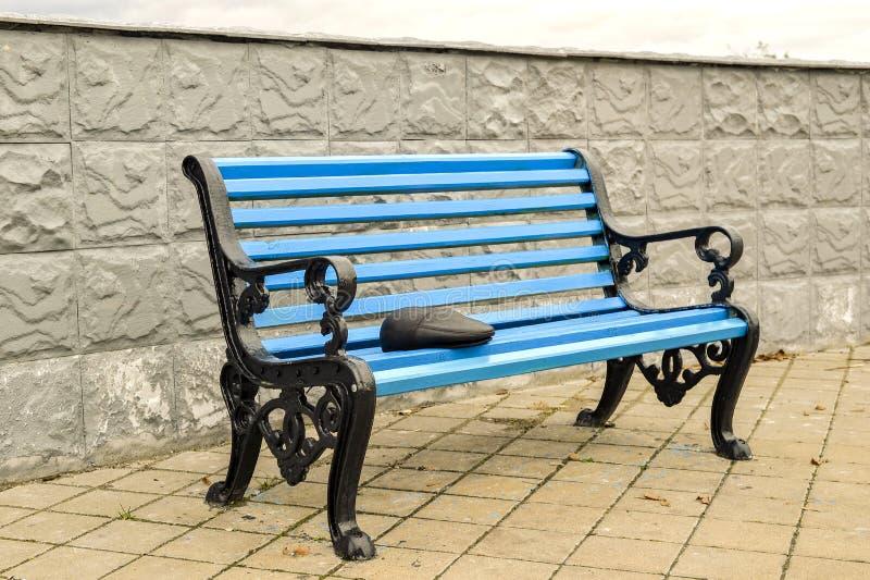 Le banc bleu en parc sur le trottoir carrelé aucun corps photo libre de droits
