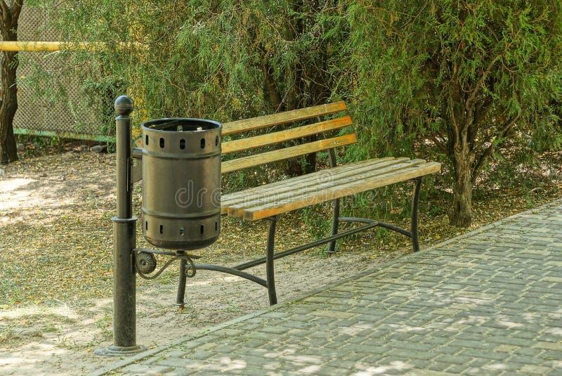 Le banc en bois de Brown et l'urne noire sont sur le trottoir en parc photos stock