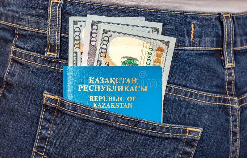 Le banconote del passaporto e del dollaro del Kazakistan nei jeans intascano immagini stock libere da diritti