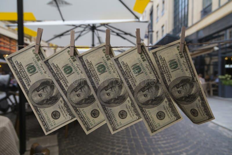 Le banconote in dollari del primo piano cento, allegate con le mollette da bucato ad una corda, appendono contro lo sfondo della  fotografia stock libera da diritti
