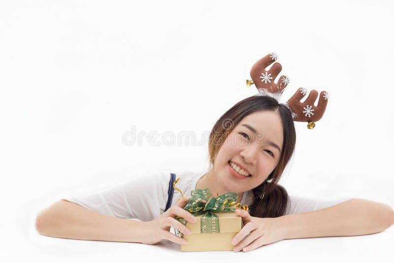 Le bandeau de port de renne de femme asiatique et juger un cadeau actuel dans le blanc ont isolé le fond photo libre de droits