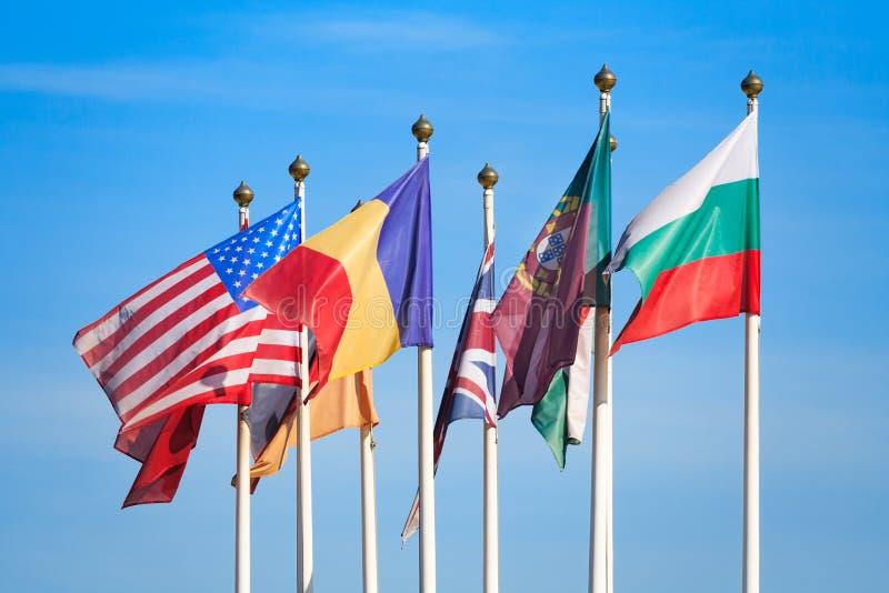 Le bandiere dei paesi differenti fluttua nel vento fotografia stock libera da diritti