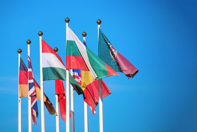 Le bandiere dei paesi differenti si sviluppano nel vento fotografia stock libera da diritti