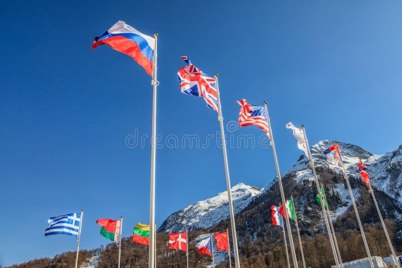 Le bandiere nazionali della Russia, del Regno Unito, di U.S.A., della Grecia e di altra ondeggiano in vento sul picco di montagne immagini stock