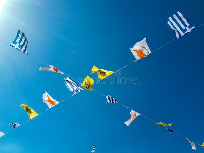Le bandiere nazionali hanno appeso su cavo su un fondo del cielo blu immagine stock