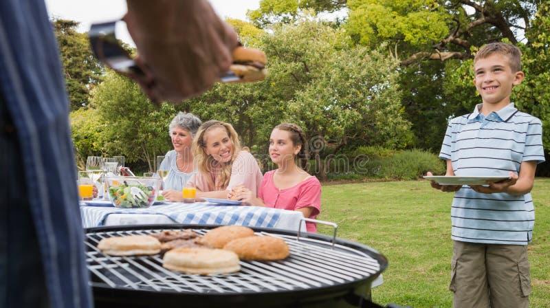 Le barbecue de attente de petit garçon a fait cuire par le père photo stock