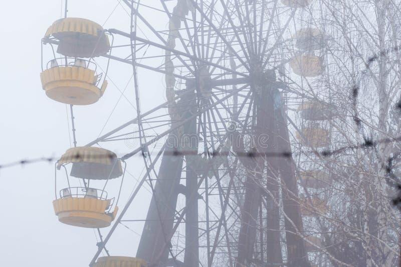 Le barbelé en métal devant l'attraction de roue de ferris en hiver brumeux a abandonné le parc d'attractions envahi avec des arbr images libres de droits