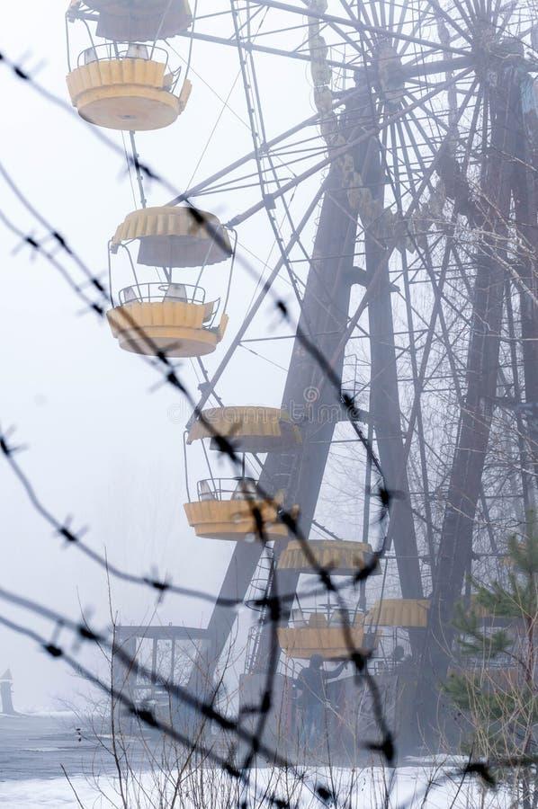 le barbelé en métal devant l'attraction de roue de ferris en hiver brumeux a abandonné le parc d'attractions envahi avec des arbr photographie stock