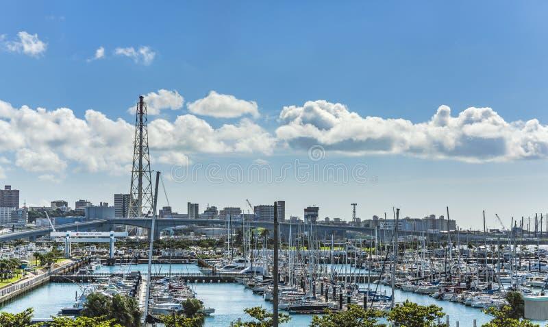 Le barche di svago hanno allineato nel porticciolo del porto di Ginowan visto dal centro di conversione di Okinawa fotografia stock