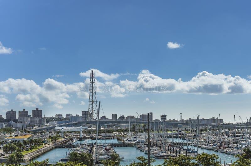 Le barche di svago hanno allineato nel porticciolo del porto di Ginowan visto dal centro di conversione di Okinawa immagine stock libera da diritti