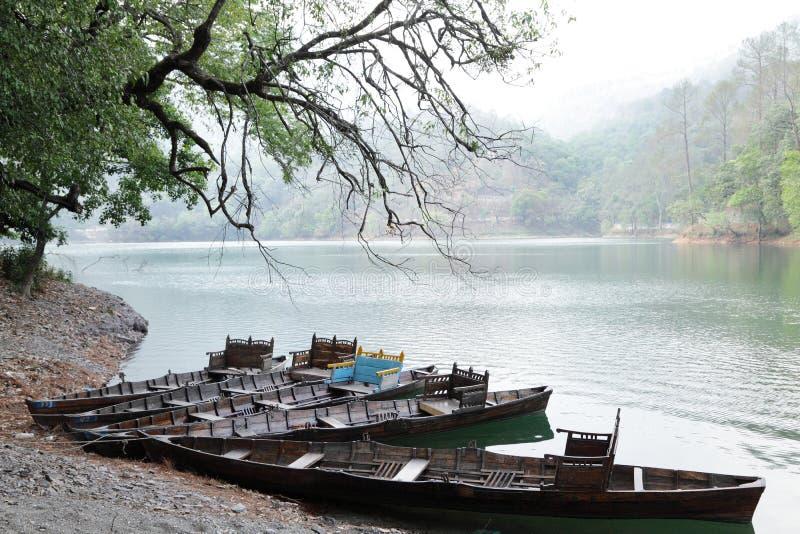 Le barche hanno parcheggiato sulla banca di bello lago Sattal immagine stock
