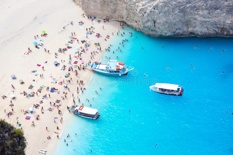 Le barche locative si avvicinano alla spiaggia con la gente Zacinto, Navagio fotografie stock