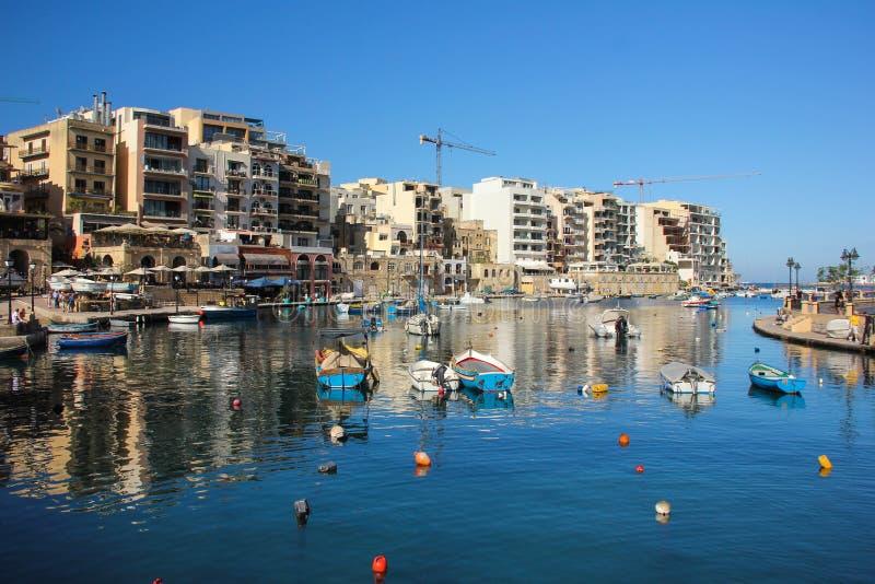 Le barche maltesi tradizionali hanno riflesso in acqua blu del porto San Giljan fotografia stock