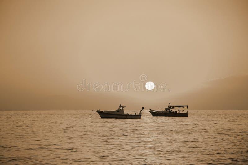 Le barche sul tramonto del mare stanno facendo galleggiare la seppia tonificata Percorso solare fotografie stock libere da diritti