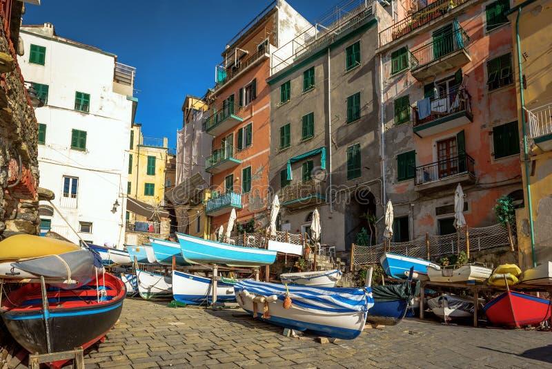 Le barche a vela variopinte alla costa della città di Riomaggiore a Cinque Terre National parcheggiano, l'Italia fotografia stock libera da diritti